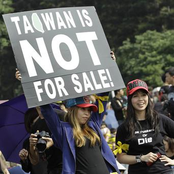 Protesters display a banner denouncing the controversial China Taiwan trade pact during a massive protest in front of the Presidential Building in Taipei (AP)