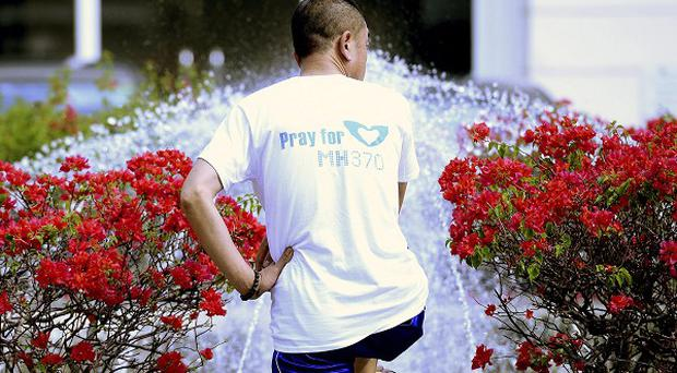 A relative of Chinese passengers on board the missing Malaysia Airlines Flight 370 stands at a fountain outside a hotel on the outskirts of Kuala Lumpur (AP)