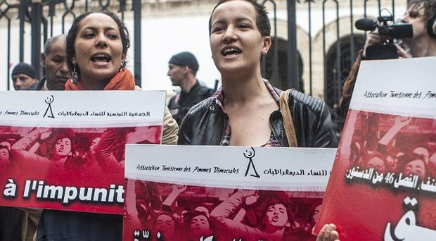 Women demonstrate outside a Tunis courthouse where three police officers faced charges of rape (AP)
