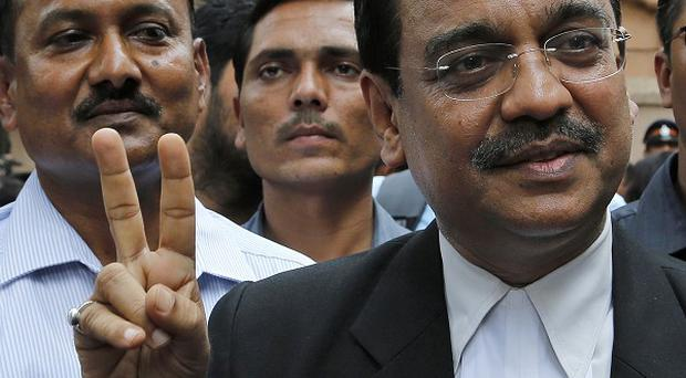 Public prosecutor Ujjwal Nikam displays the victory symbol as he comes out of a court in Mumbai, India (AP)