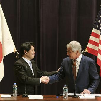 Japanese defence secretary Itsunori Onodera and US defence secretary Chuck Hagel shake hands during a joint press conference in Tokyo (AP)