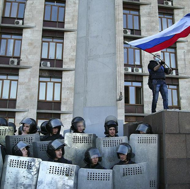 A pro-Russian masked activist waves a Russian national flag above Ukrainian police at the regional administration building in Donetsk (AP)
