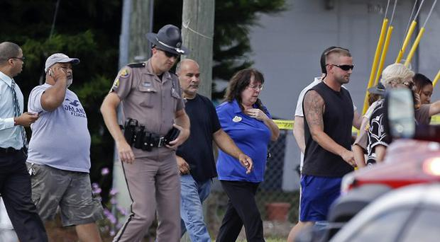 A Florida state trooper escorts a group of parents to pick up their children after a car crash injured 12 youngsters (AP)