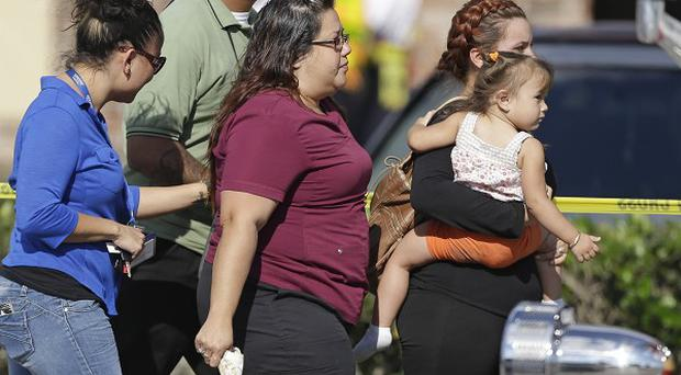Parents and relatives leave the day care centre with their children after the crash (AP)