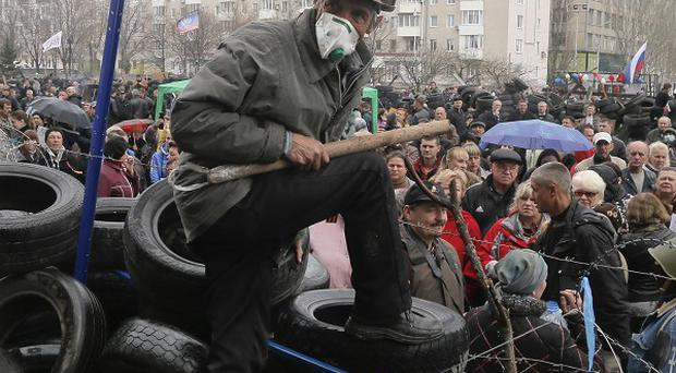 Pro-Russian activists at a barricade during a rally at the regional administration building in Donetsk (AP)