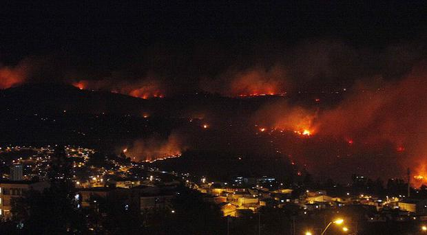 An out of control forest fire rages towards urban areas in the city of Valparaiso, Chile