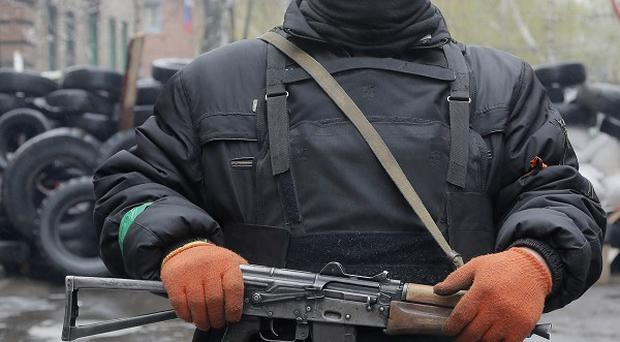 A pro-Russian gunman stands guard at a seized police station in the eastern Ukraine town of Slovyansk. (AP)