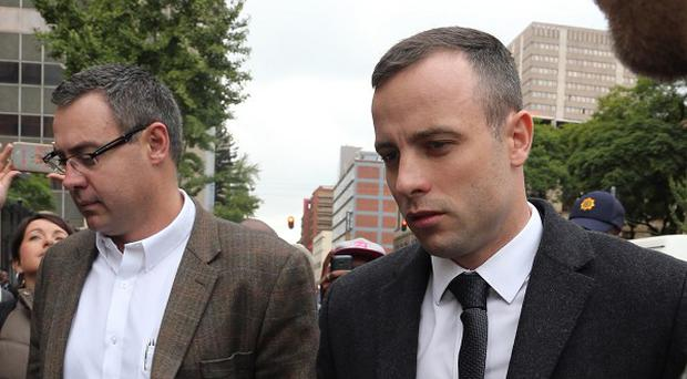 Oscar Pistorius arrives at the High Court in Pretoria, South Africa, as his trial for the murder of his girlfriend, Reeva Steenkamp, continues (AP Photo/Themba Hadebe)