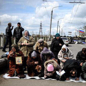 Women pray for peace near a regional administration building seized by pro-Russian activists in Slovyansk (AP)