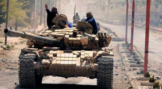 Syrian army soldiers sit on their tank while on patrol in a village north-east of the capital Damascus. (AP/SANA)