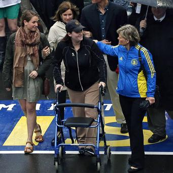 Boston Marathon bombing survivor Erika Brannock, and her mother, Carol Downing, at right, walk across the Marathon finish line after a remembrance ceremony in Boston (AP)
