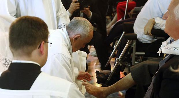 Pope Francis kneels to wash the feet of 12 elderly and disabled people in a Holy Thursday ritual (AP Photo/Riccardo De Luca)