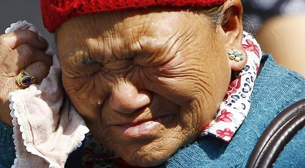 Mother of Nepalese mountaineer Ang Kaji Sherpa, killed in an avalanche on Mount Everest, cries while she waits for his body at Sherpa Monastery in Katmandu