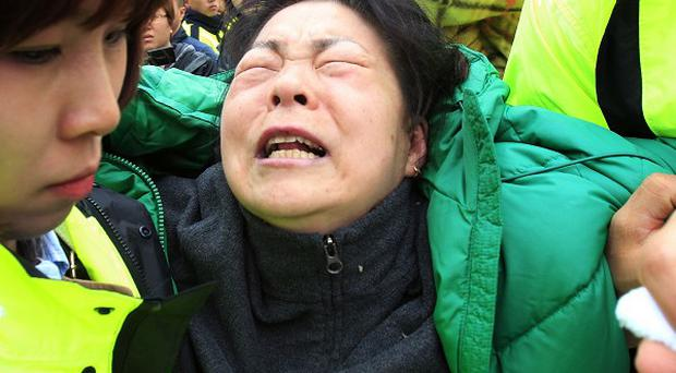 A relative of a passenger aboard the sunken ferry Sewol weeps as she waits for her missing loved one at a port in Jindo, South Korea (AP)