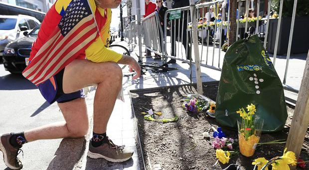 Ron McCracken, from Dallas, pays his respects at a makeshift memorial in Boston honouring the victims of the 2013 marathon bombings (AP)