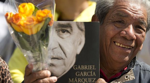 A well-wisher holds an autobiography of Gabriel Garcia Marquez, as he waits to pay his respect to the beloved author (AP)