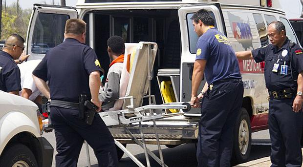 A 15-year-old boy who stowed away in the wheel well of a flight from San Jose, California, to Maui, is put into an ambulance at Kahului Airport (AP/The Maui News)