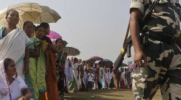 A security man stands guard as women wait in a queue to cast their votes during the sixth phase of polling of the Indian parliamentary elections in Sonapur village on the outskirts of Gauhati (AP)