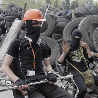 Pro-Russian activists guard a barricade at the regional administration building in Donetsk, Ukraine (AP)