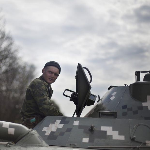 A Ukrainian soldier sits atop his armoured vehicle at a checkpoint near the village of Artemiovska, around 14 miles from Slovyansk, Ukraine (AP)