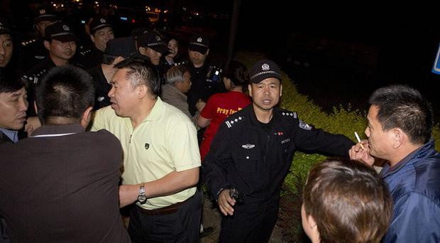 Chinese police try to prevent relatives of passengers on board Malaysia Airlines MH370 from marching to the Malaysian embassy (AP)