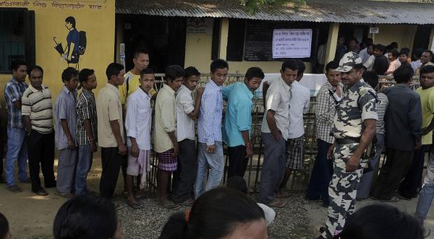 Security personnel stand guard as people wait to cast their votes outside a polling station in Sonapur village, on the outskirts of Gauhati, India (AP)