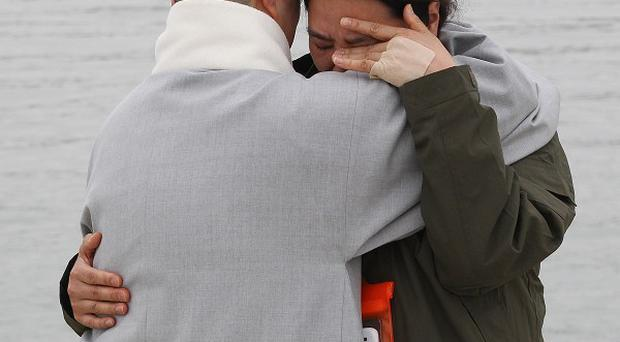 A relative of a passenger aboard the sunken ferry Sewol is consoled by a Buddhist nun, left, as she waits for news (AP)
