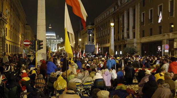 Pilgrims gather in via della Conciliazione, in front of St Peter's Square as they wait for the canonisation of Pope John XXIII and Pope John Paul II (AP)