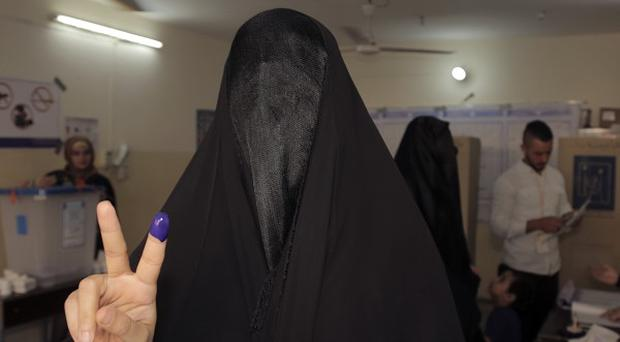 An Iraqi woman gives the victory sign while showing her inked finger after casting her vote at a polling station Baghdad (AP)