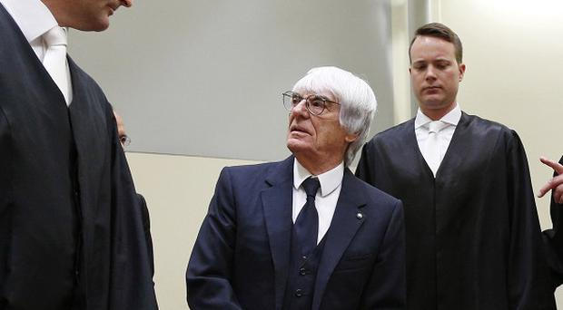 Formula One boss Bernie Ecclestone, 2nd left, looks up at one of his lawyers, Norbert Scharf, left, as he arrives at court in Munich (AP Photo/Matthias Schrader, pool)