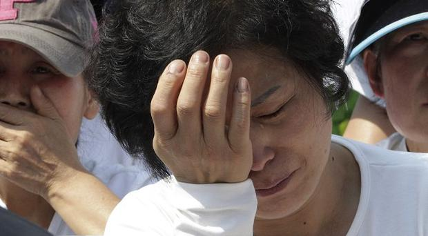 Workers weep during a May Day rally in Seoul to pay tribute to the victims of the sunken ferry (AP)