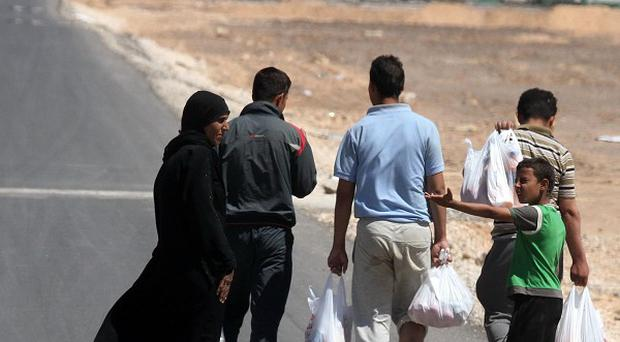 A Syrian refugee family walks towards the new Syrian camp of Azraq, 55 miles from the Syrian border in Jordan (AP)