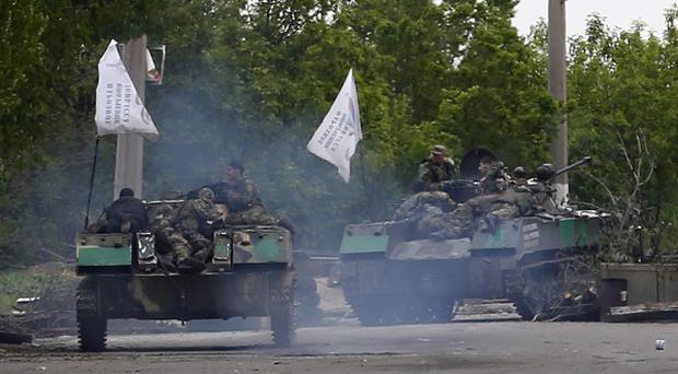 Pro-Russian gunmen atop armoured carriers pass by barricades on a road leading into Slovyansk, eastern Ukraine (AP)