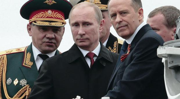 Russian President Vladimir Putin, flanked by Defence Minister Sergei Shoigu (left) and Federal Security Service chief Alexander Bortnikov, arrives on a boat after inspecting battleships during a navy parade marking the Victory Day yesterday