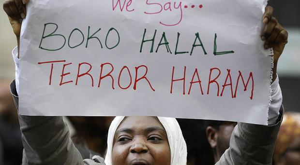 Demonstrators hold banners as they protest about the kidnapping of girls in Nigeria, near the Nigerian High Commission in London (AP)