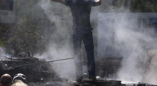 A local man stands atop a seized armoured patrol car that was set alight in the centre of Mariupol, eastern Ukraine (AP)
