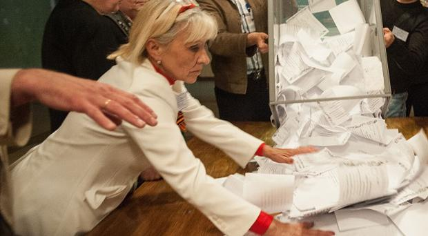 Members of election committee empty a ballot box after voting closed at a polling station in Donetsk, Ukraine (AP)