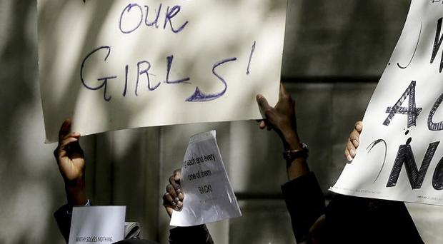 Demonstrators hold banners as they protest about the kidnapping of girls in Nigeria (AP)