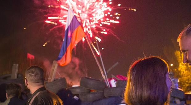 People watch fireworks celebrating the declaration of independence for Donetsk region with a Russian national flag is in the background (AP)