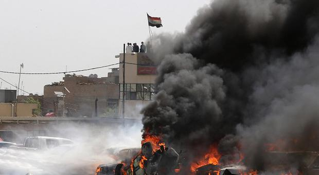 Iraqi firefighters try to extinguish burning vehicles after a car bombing in Sadr City, Baghdad (AP)