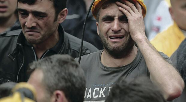 A miner breaks down in tears as rescue workers carry the dead body of a colleague from the mine in Soma