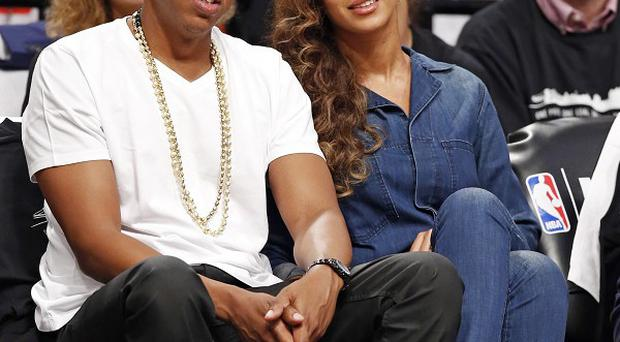 Jay Z and Beyonce watching a basketball game in New York (AP)
