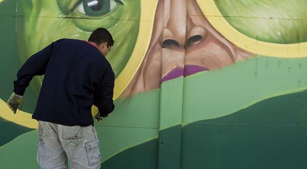 Murals are being painted by Brazilian artists near the Itaquerao stadium but prosecutors are threatening to halt work at the ground (AP)