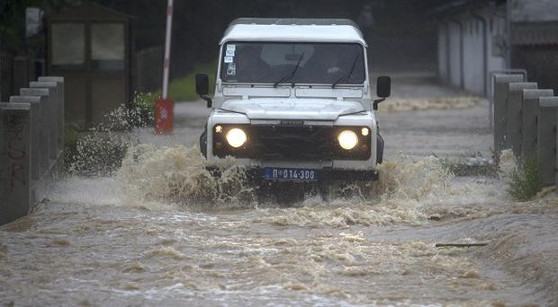 A police vehicle struggles as it goes through overflowing waters in a suburb of Belgrade, Serbia. (AP)