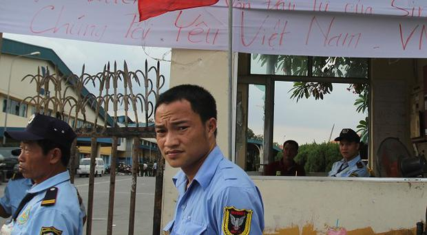 Security staff guard a factory in Vietnam, after mobs attacked foreign owned factories following anti-China protests (AP)
