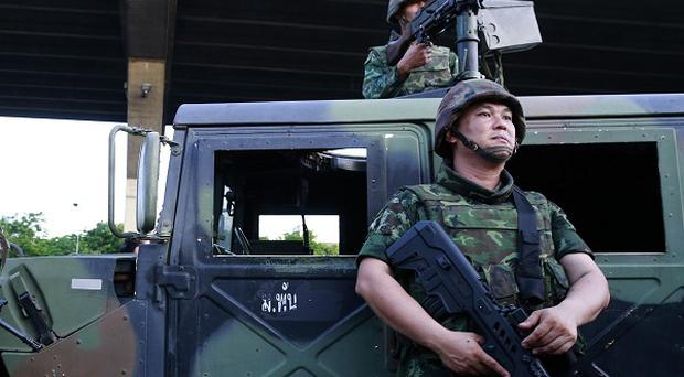 Soldiers take up position outside the Centre for the Administration of Peace and Order in Bangkok after Thailand's army declared martial law (AP)