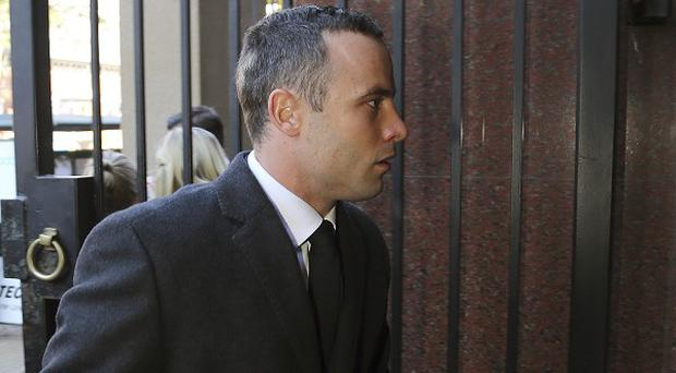 Oscar Pistorius arrives at the High Court in Pretoria, South Africa, where he is on trial for the murder of his girlfriend Reeva Steenkamp on Valentine's Day 2013 (AP)