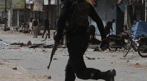 A Pakistani police commando rushes to the site of an explosion in Karachi, Pakistan (AP)
