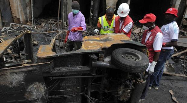 Red cross officials inspect a vehicle at the scene of Tuesday's car bomb explosions in Jos, Nigeria (AP)