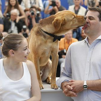 Actress Zsofia Psotta, left, looks on as director Kornel Mundruczo is licked in the face by a dog during a photo call for White God (AP)